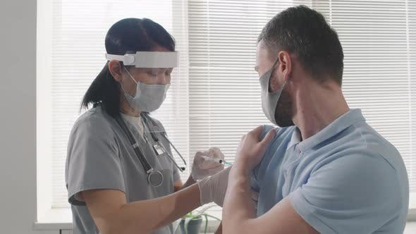 Nurse Giving Vaccination Dose To Patient