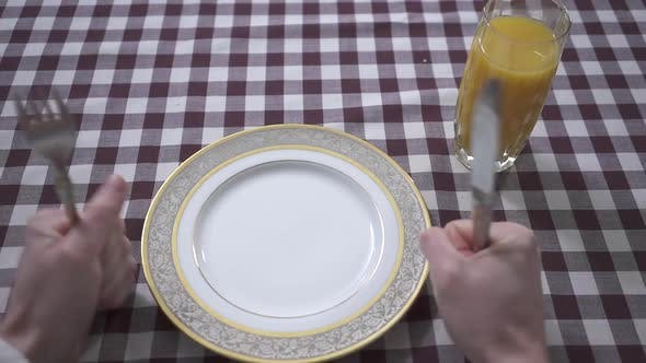 Cover Image for Man's Hand Knocking on the Table with His Fists with Fork and Knife, Demanding Food