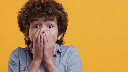 Studio Portrait of Amazed Little Boy Closing Mouth in Fear, Looking Frightened