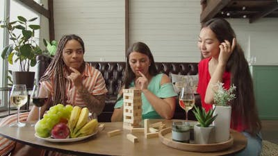 Mixed Race Female Friends Playing Wooden Board Game Sitting Indoors