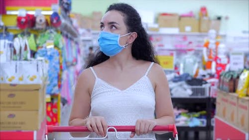 Young Woman in a Mask From a Coronavirus Epidemic Is Standing in the Grocery Department of the