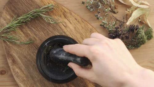 The Women Pounding Spices and Herbs in Mortar for Food Cooking Hold Pestle with Mortar