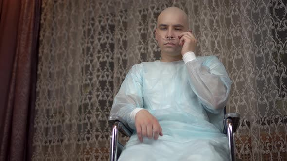 Thumbnail for A Bald Young Man with Oncology Looks Sadly at the Camera. The Patient Adjusts the Breathing