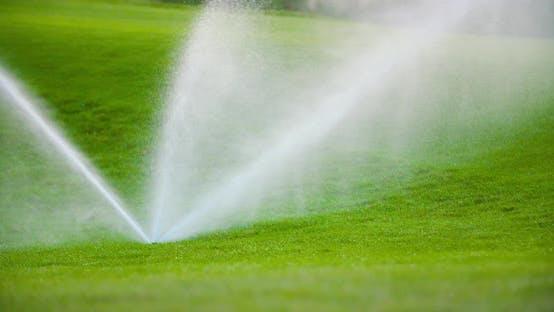 Thumbnail for Medium Shot of Grass Sprinkler Splashes Water Over the Lawn