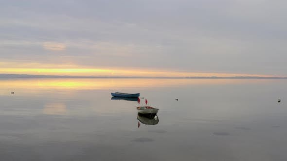 Thumbnail for Two Rowboats While Sun Rises in the Background