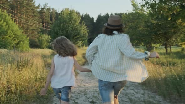 Cover Image for Mother and Daughter Running Holding Hands, Back View
