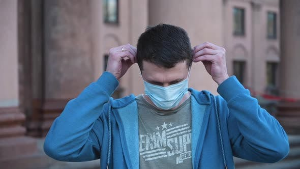 Portrait of Caucasian Man Putting Medical Mask on Face
