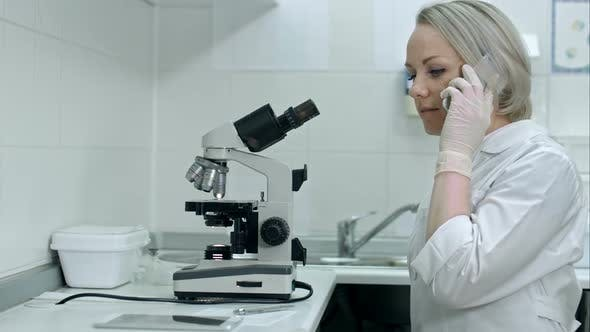Thumbnail for Female Lab Worker with White Coat Using Mobile Phone at His Workplace in the Laboratory