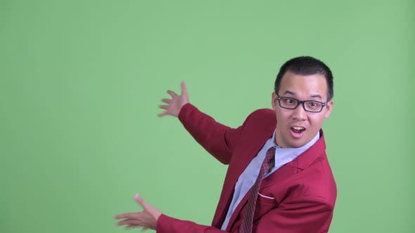 Thumbnail for Happy Asian Businessman with Eyeglasses Showing To the Back and Looking Surprised