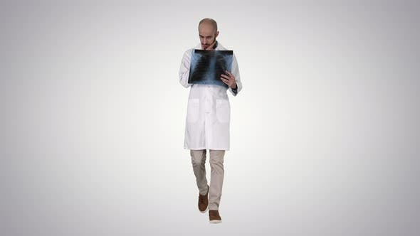 Thumbnail for Doctor Radiologist Looking at X-ray Scan Walking on Gradient Background