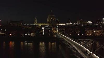 People Walking Across Millennium Bridge at Night