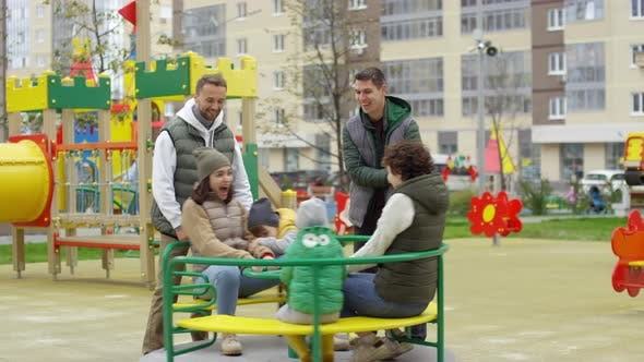 Thumbnail for Young Families Having Fun on Merry-Go-Round at Playground