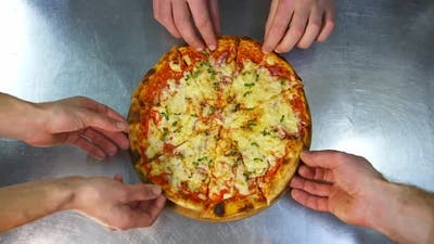 Hands Taking Slices Of Pizza. Hands taking pizza slices from wooden plate