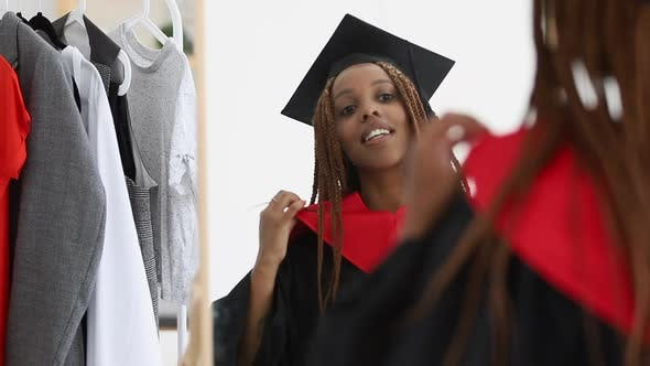 Woman Put on Graduate Cap and Gown and Look in Mirror Spbi