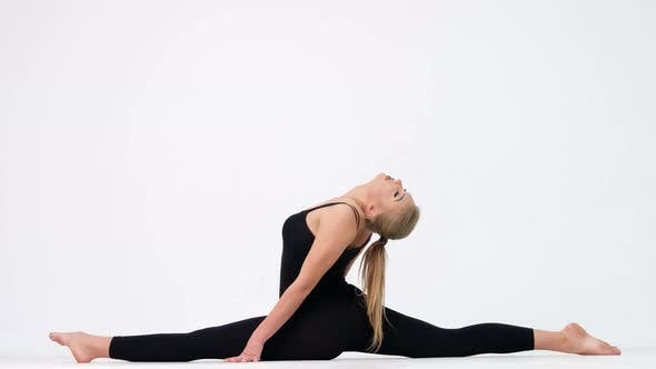 Young woman demonstrates a yoga pose on a white background.