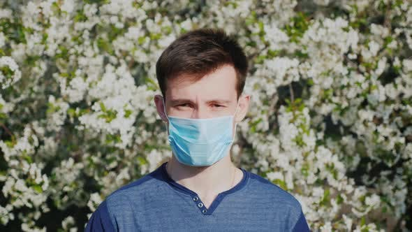 Thumbnail for A Man in a Gauze Bandage Against a Background of Flowering Trees. Allergy During the Spring