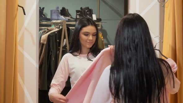 Thumbnail for Charming Young Woman Trying Clothes in Front of a Mirror at Clothing Store