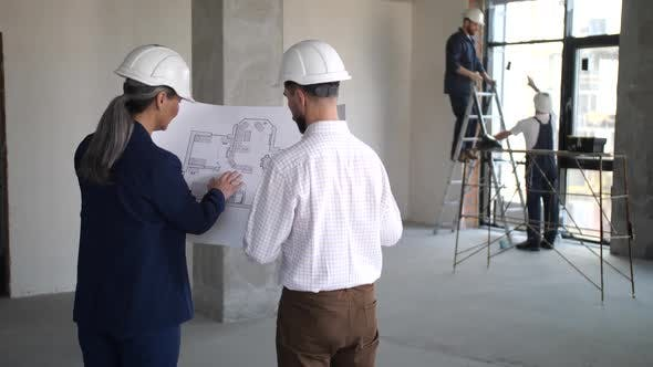Designers Holding Blueprint with Apartment Layout
