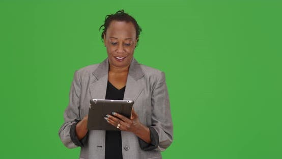 Thumbnail for A black businesswoman happily uses a tablet and talks to camera on green screen