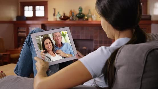 Thumbnail for Young white woman talking to her parents via video chat