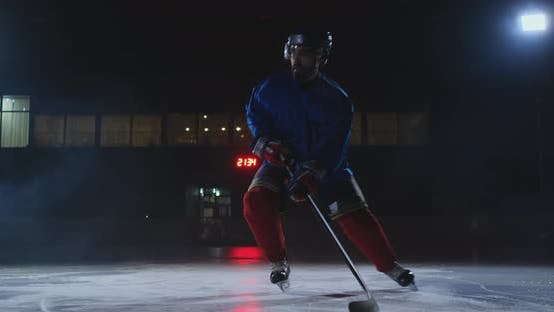 Cover Image for Male Hockey Player with a Puck on the Ice Arena Shows Dribbling Moving Directly Into the Camera