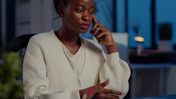 Nervöser afrikanischer Manager diskutiert mit Mitarbeiter am Smartphone