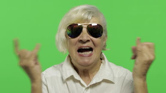 Thumbnail for An Elderly Woman Show Sign of the Horns with Her Hands and Showing Tongue