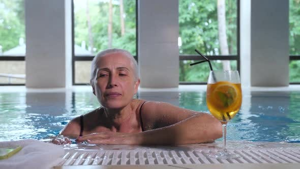 Thumbnail for Mature Woman Swimming To Pool Side in Spa Hotel