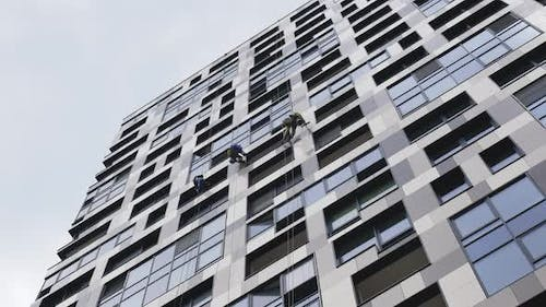 Industrial Climbers Cleaning the Exterior Windows of a High Rise Building with Blue Sky and Clouds