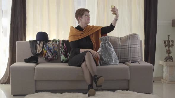 Thumbnail for Adult Attractive Caucasian Woman Talking To Subscribers Via Smartphone. Pretty Lady Sitting on Sofa