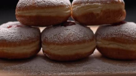 Thumbnail for Close up of hanukkah doughnuts on a wooden board, slow motion