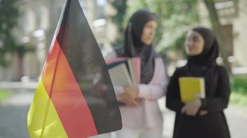 Close-up of German Flag Fluttering Outdoors with Two Muslim Women Talking at the Background. Happy