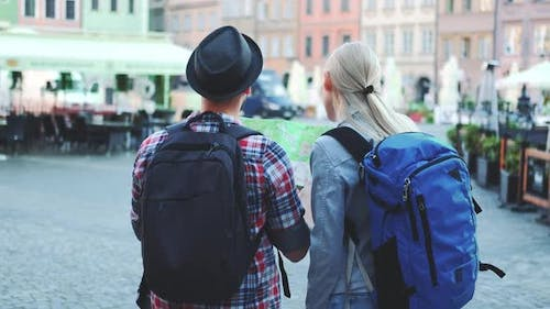 Man and Woman with Bags Checking Map on Central City Square