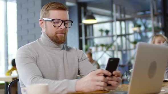 Cover Image for Cheerful Caucasian Man Texting on Phone and Smiling for Camera in Cafe