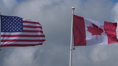 The national USA and canadian flags waving in the wind.