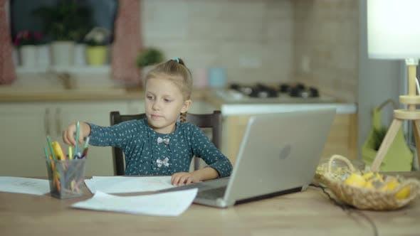 Little Girl zeichnet auf Papier mit Bleistiften Zeichnungen zu Hause