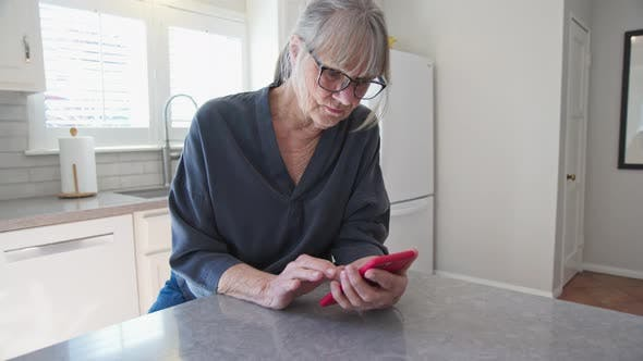Thumbnail for Senior woman text messaging on smartphone while sitting at kitchen counter
