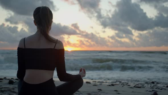 Young Woman Meditates on the Seashore Against the Background of Sunset