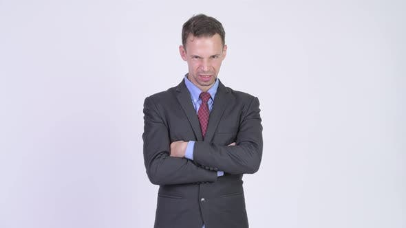 Thumbnail for Studio Shot of Angry Businessman with Arms Crossed