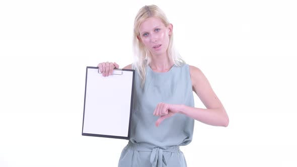 Thumbnail for Stressed Young Blonde Woman Showing Clipboard and Giving Thumbs Down