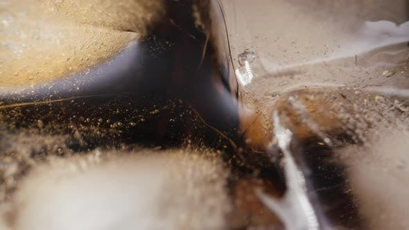 Pouring Cola with Ice Cubes Closeup
