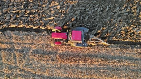 Roter Traktor mit im Feld zum Pflügen von Land Luftaufnahme eines landwirtschaftlichen Feldes