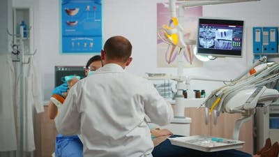 Dentist Drilling Woman Tooth in Dental Clinic