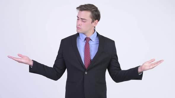 Cover Image for Young Handsome Businessman Comparing Something