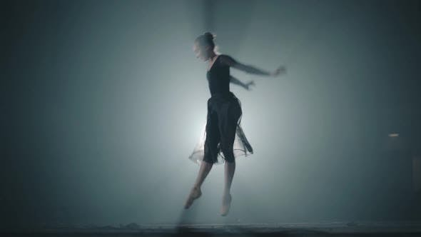 Thumbnail for Graceful Professional Ballerina Dancing in Ballet Shoes and Black Dress in the Studio in Spotlight