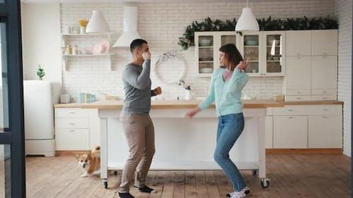 Joyful Man and Woman with Corgi Dog Crazy Fun Dancing at Home