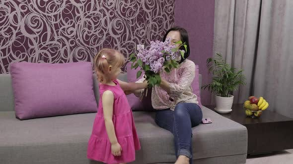 Little Daughter Child Congratulates Her Mother with Bouquet of Lilac Flowers