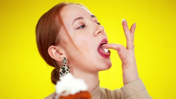 Closeup of Funny Greeneyed Redhead Caucasian Woman Licking Topping Cream of Fingers and Smiling