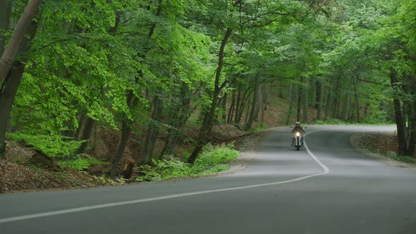 Thumbnail for Riding a motorcycle on a road through forest