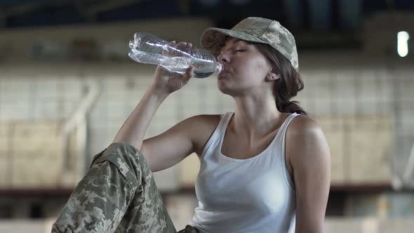 Thumbnail for Cute Young Woman in Military Uniform Drinking Water From the Bottle Sitting on the Floor in Dusty
